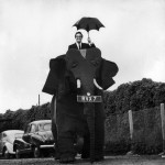 British actor and comedian Peter Sellers (1925 – 1980) smiles and holds an umbrella as he drives his nearly full-size mechanical elephant, Chipperfield, England, 1960.