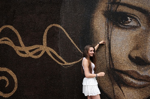 A beautiful assistant of the artist next to Coffee bean painting 'Awakening', which entered the Guinness Book record