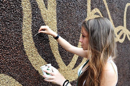 A girl inserting coffee beans. Wall mural 'Awakening' by Moscow artist Arkady Kim – a new Guinness Book record