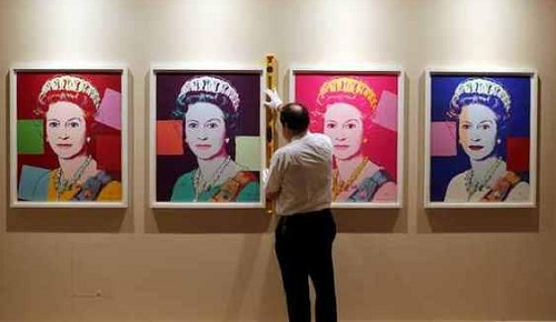 Trust Exhibition Conservator David Westwood hangs portraits of Queen Elizabeth II by Andy Warhol as part of the exhibition The Queen: Portraits of a Monarch being shown at Windsor Castle. November 20, 2012