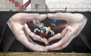 Two hands manipulating a Pinocchio puppet, street art by German artist Andreas von Chrzanowski (Case), Frankfurt, Germany.