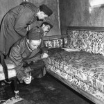 War correspondents examining the arm of sofa stained with blood while one of them uses a candle to search the floor for evidence of suicide in Adolf Hitler's underground shelter