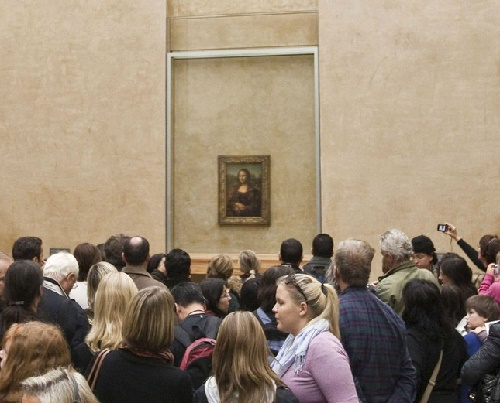 Visitors watch Leonardo da Vinci's Mona Lisa 03 April 2001 in the Louvre museum in Paris. The painting had been hung in a different room for the past two years whilst the original room was renovated
