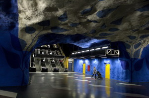 Station T-Centralen. The walls are painted in blue, blue painted vaults have images of branches with leaves and silhouettes of construction workers.