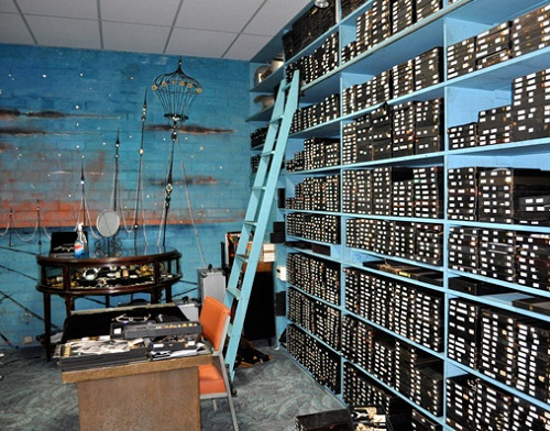 A small (100 sq ft) room painted in turquoise color. Racks around the room from floor to ceiling crammed with boxes of ornaments.