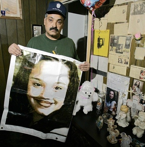 Felix DeJesus, holding a banner showing his daughter's photograph, standing by a memorial in his living room in Cleveland in 2004
