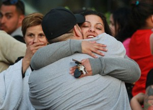 Two people hug outside the hospital. Crowds of Cleveland residents gathered at the police station and cheered as squad cars pulled into the station Monday night