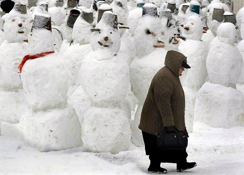 February 2, 2015. A woman walks past a hundred of snowmen in the center of Moscow