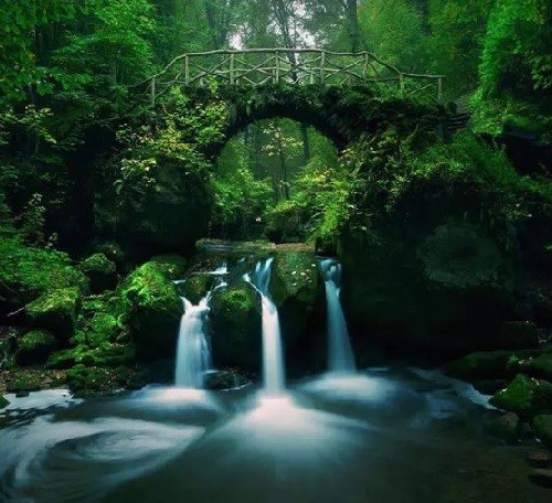 Old stone bridge at Schiessentümpel waterfall, in Müllerthal, Luxembourg
