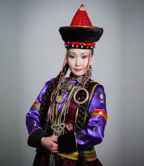 Bright folk costume of Buryat woman decorated with massive jewelry