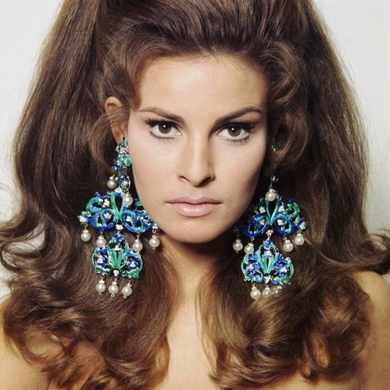 Wearing massive chandelier earrings Raquel Welch